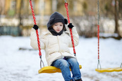 Adorable girl having fun on a swing on winter day Stock Image