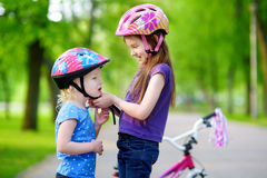 Adorable girl helping her sister to put a bicycle helmet on Royalty Free Stock Photo