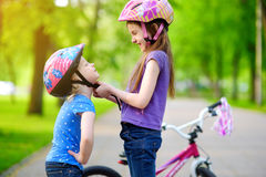 Adorable girl helping her sister to put a bicycle helmet on Stock Images