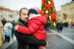 Adorable girl and her father having wonderful time on traditional Christmas market. Parent and child enjoying themselves near Chri stock photography