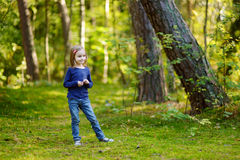 Adorable girl hiking in the forest on autumn day Stock Photo