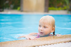 Adorable girl hold at pool side in tropical beach resort Royalty Free Stock Photo