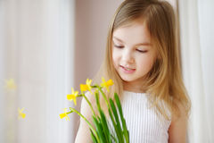 Adorable girl holding daffodils by the window Stock Images