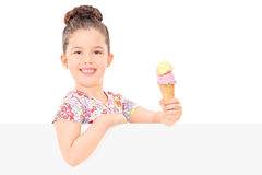 Adorable girl holding ice cream behind a panel Royalty Free Stock Image