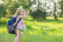 Adorable girl with huge backpack walking in park Stock Photos