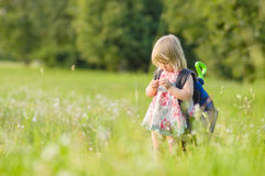 Adorable girl with huge backpack walking in park Royalty Free Stock Images