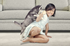Adorable girl and husky puppy at home Royalty Free Stock Image