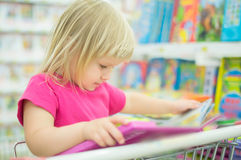 Adorable girl with interactive book on cart Royalty Free Stock Image