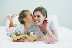 Adorable girl kissing her mother lying on a bed Royalty Free Stock Photography