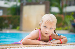 Adorable girl lie on pool side in tropical beach resort Royalty Free Stock Images