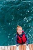 Adorable girl in life jacket. Adorable girl wearing life jacket at sea royalty free stock image