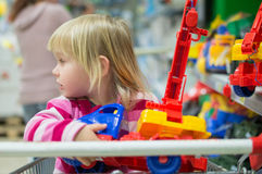 Adorable girl look to toys sit in shopping cart Stock Photo