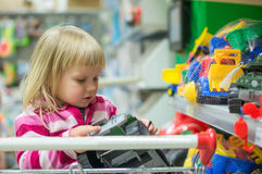 Adorable girl look to toys sit in shopping cart Stock Photography