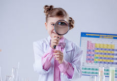 Adorable girl looking through magnifying glass Royalty Free Stock Photo