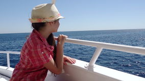 Adorable girl looking to the blue sea from yacht board. Adorable girl in hat looking to the blue sea from yacht board in sunny day stock video