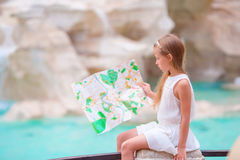 Adorable girl looking at touristic map near Trevi Fountain, Rome. Happy toodler kid enjoy italian vacation in Europe. Royalty Free Stock Images