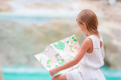 Adorable girl looking at touristic map near Trevi Fountain, Rome. Happy toodler kid enjoy italian vacation in Europe. Stock Photography