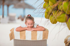 Adorable girl on lounger at tropical exotic beach under big coconuts Stock Photo