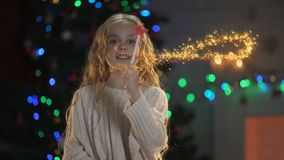 Adorable girl with magic wand making miracles, X-mas decor sparkling behind. Stock footage stock video