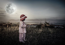 Adorable girl in night sky under beautiful full moon. Vintage to. Asian child relaxing outdoors with bright full moon at night, travel on vacation. Adorable girl Royalty Free Stock Images