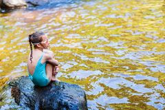 Adorable girl outdoors. Little girl outdoors sitting in swimsuite by a water pond, lake or river royalty free stock photo