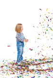 Adorable Girl in Overalls. Cute little blond girl with burst of sparkling confetti against white background, tossing it up and watching it fall down smiling Royalty Free Stock Images