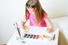 Adorable girl painting with watercolor in a sunny white room at. Adorable girl painting with watercolor in a sunny white room Stock Photography