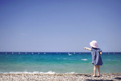 Adorable girl on a pebble beach Royalty Free Stock Photos