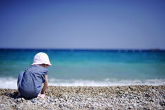 Adorable girl on a pebble beach Royalty Free Stock Image