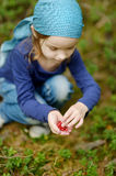 Adorable girl picking foxberries in the forest Stock Photo