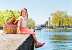 Adorable girl with picnic basket on embankment royalty free stock image