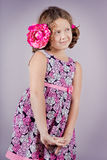 Adorable girl with a pink flower in her hair Stock Images
