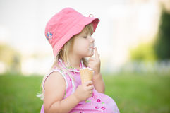 Adorable girl in pink hat eat ice cream on grass Stock Photo