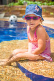 Adorable girl with pink sunglasses and blue hat sit in pool on s Stock Photo