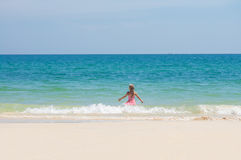 Adorable girl in pink swimming suit run to ocean through waves Royalty Free Stock Photos