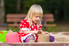 Adorable girl play with toys on sandbox Royalty Free Stock Images