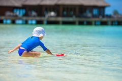 Adorable girl playing with beach toys during. Adorable little girl playing with beach toys during summer vacation Stock Photo