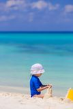 Adorable girl playing with beach toys during. Adorable little girl playing with beach toys during summer vacation Royalty Free Stock Photos