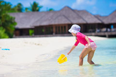 Adorable girl playing with beach toys during Stock Photos