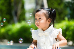 Adorable girl playing bubble blower Stock Photos