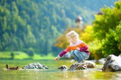 Free Adorable Girl Playing By Konigssee Lake In Germany On Warm Summer Day. Cute Child Having Fun Feeding Ducks And Throwing Stones Int Royalty Free Stock Image - 113187956