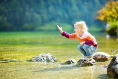 Free Adorable Girl Playing By Konigssee Lake In Germany On Warm Summer Day. Cute Child Having Fun Feeding Ducks And Throwing Stones Int Stock Images - 113259784