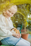 Adorable girl playing with cavy looking at camera Stock Images
