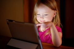 Adorable girl playing with a digital tablet in a dark room Royalty Free Stock Photo