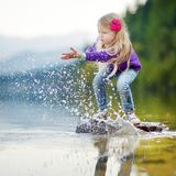Adorable girl playing by Hallstatter See lake in Austria on warm summer day. Cute child having fun splashing water and throwing st. Ones into the lake. Summer royalty free stock image
