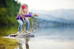 Adorable girl playing by Hallstatter See lake in Austria on warm summer day. Cute child having fun splashing water and throwing st Stock Photo