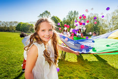 Adorable girl playing parachute with her friends. Portrait of adorable blonde girl playing parachute and balls with her friends in the summer park Stock Image