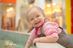 Adorable girl playing in a public fountain Stock Photo