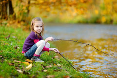 Adorable girl playing by a river on autumn day Royalty Free Stock Images
