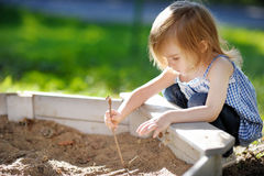 Adorable girl playing in a sandbox Royalty Free Stock Photo